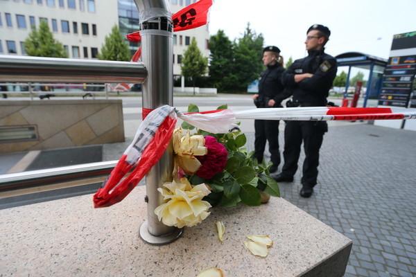 Blumen liegen am 23.07.2016 am Zugang zur U-Bahnstation Olympia-Einkaufszentrum in München (Bayern), den die Polizei nach einer Schießerei mit Toten und Verletzten am Vortag abgesperrt hat. Die tödlichen Schüsse hat ein 18-jähriger Deutsch-Iraner abgegeben. Zehn Menschen starben, darunter der Täter. Der Schütze, ein 18-jähriger Deutsch-Iraner, habe mit hoher Wahrscheinlichkeit alleine gehandelt und sich danach selbst erschossen, teilten die Ermittler am frühen Samstagmorgen mit. Foto:Karl-Josef Hildenbrand/dpa |/ Picture Alliance, rankfurt/Main